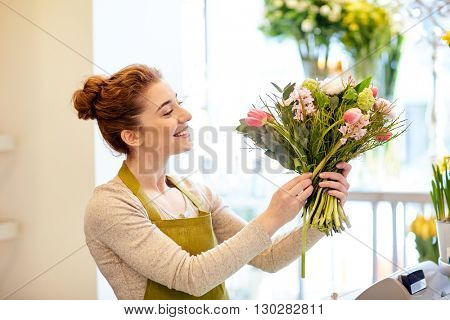 people, business, sale and floristry concept - happy smiling florist woman making bunch at flower shop