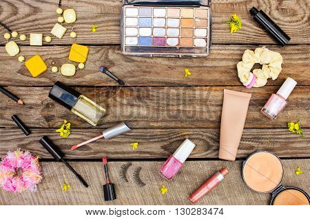Cosmetics: mascara, beads, elastic hair band, false eyelashes, concealer, nail polish, perfume, eyeliner, powder, lip gloss, eye shadow and yellow flowers on wooden background. Toned image.