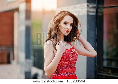 Close Up Portrait Of Fashionable Girl At Red Evening Dress Posed Background Mirror Window Of Modern