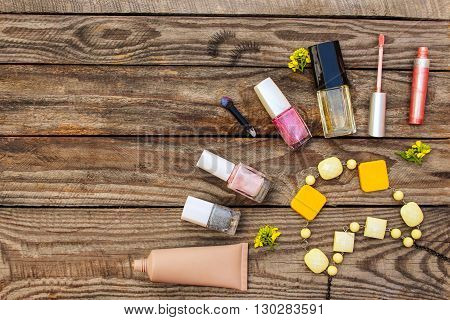 Cosmetics:, false eyelashes, concealer, nail polish, perfume, lip gloss, beads, and yellow flowers on wooden background. Toned image.