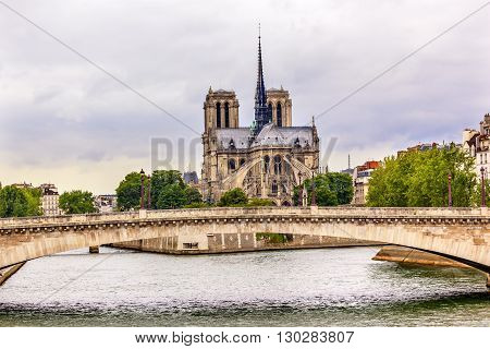 Flying Butresses Spires Towers Seine River Bridge Overcast Skies Notre Dame Cathedral Paris France. Notre Dame was built between 1163 and 1250 AD. Black Spire erected in the 1850s.