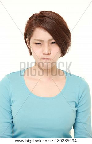 portrait of young Japanese woman in a bad mood on white background