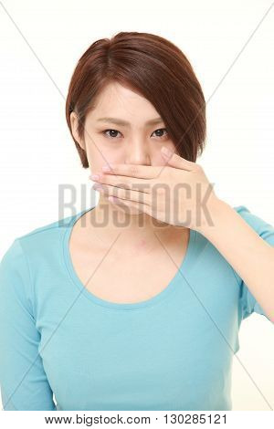 portrait of Japanese woman making the speak no evil gesture on white background