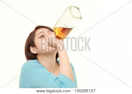 portrait of young Japanese woman drinking straight from a bottle on white background