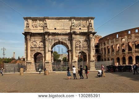 ROMA ITALY APRIL 7 2016 : Tourists visiting Arco de Constantino (Arch of Constantine) and Colosseum. The arch was erected by the Roman Senate to commemorate Constantine victory over Maxentius
