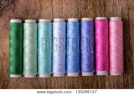 cotton sewing from green to pink on wood