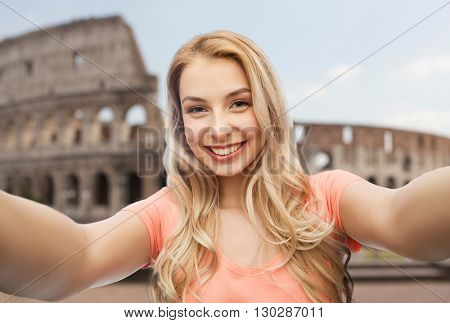 travel, tourism, emotions, expressions and people concept - happy smiling young woman taking selfie over coliseum background