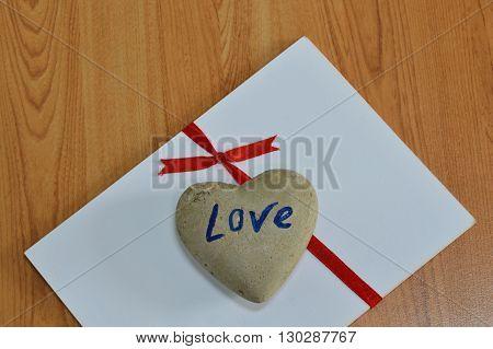 rock in heart shape on white paper tie red ribbon