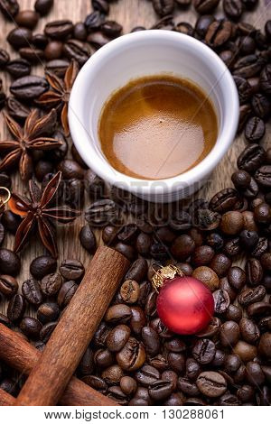 cup of coffee with coffee beans, cinnamon, star anise and red christmas ball on wood
