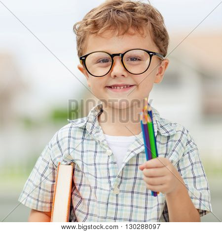 Portrait of Beautiful school boy looking very happy outdoors at the day time. Concept school theme.