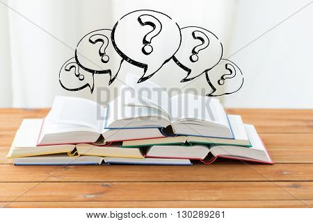 education, school, literature, reading and knowledge concept - close up of books on wooden table and question marks