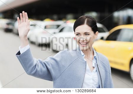 travel, business trip, people, gesture and tourism concept - smiling young woman over taxi waving hand at airport terminal or railway station