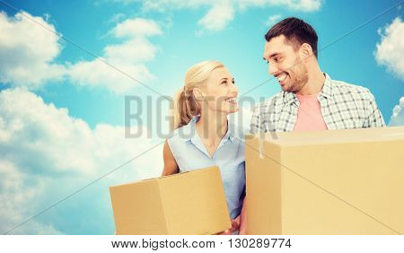 home, people, delivery and real estate concept - happy couple holding cardboard boxes over blue sky and clouds background