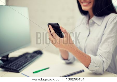 business, education, technology and people concept - close up of happy woman with notebook and computer texting on smartphone at office