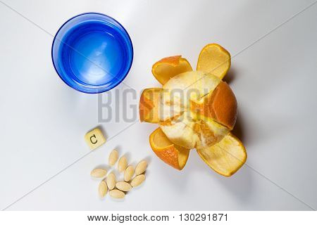 Top view of C vitamin pils orange and glass of water on white
