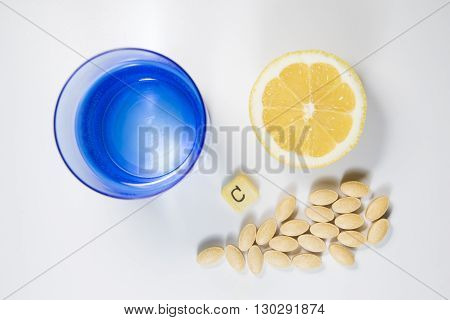 Top view of C vitamin pils lemon and glass of water on white