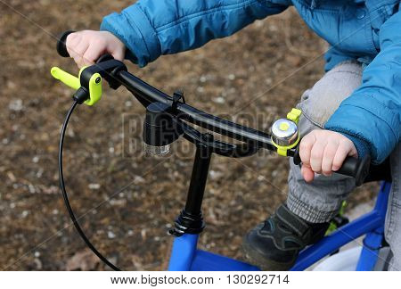 The image of the child who is riding a children's Bicycle. Front view. The child's hands control the wheel of the bike.