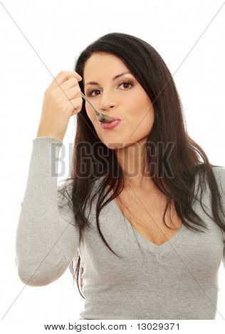 Portrait of young smiling woman with spoon in her mouth and (pleasure from eating), isolated on white