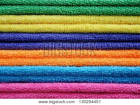 Terry towels of different colors stacked in a pile as background