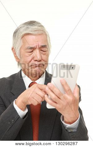 portrait of senior Japanese businessman using tablet computer looking confused on white background