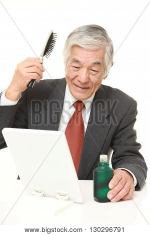 portrait of senior Japanese businessman using hair restorer on white background