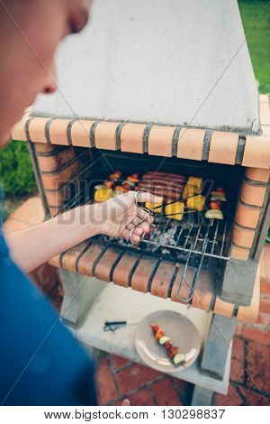 Back view of unrecognizable young man cooking sausages, corn and vegetable skewers in a brick barbecue