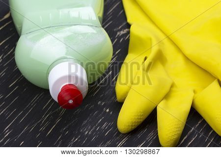 Detergent and latex gloves on wooden background