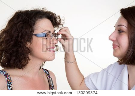 Optician Putting A New Pair Of Eyeglasses On A Female Patient