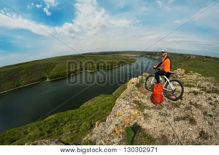 Cyclist in Orange Wear Riding the Bike Down Rocky Hill under River. Travel Concept