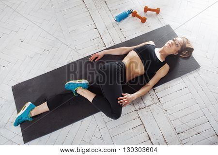 Beautiful young slim woman  doing stretching exercises at the gym