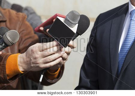 Journalists holding a microphones conducting TV or radio interview