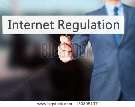 Internet Regulation - Businessman Hand Holding Sign