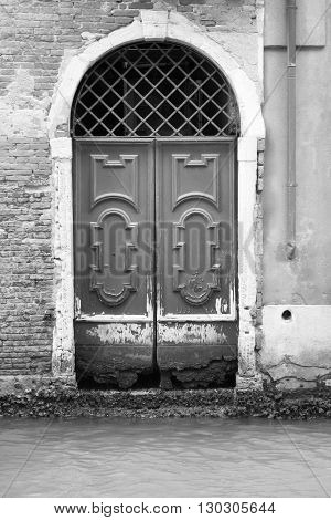 old and ancient wooden doors or gate closeup for a vintage architectural background of monochrome tone