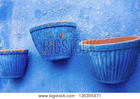 empty three flowerpot are located separately on the plastered wall closeup for vintage interior