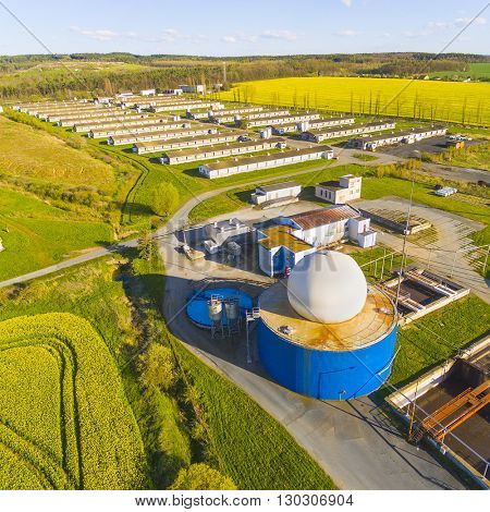 Aerial view to biogas plant from pig farm in rapeseed fields. Renewable energy from biomass. Modern agriculture in Czech Republic and European Union.