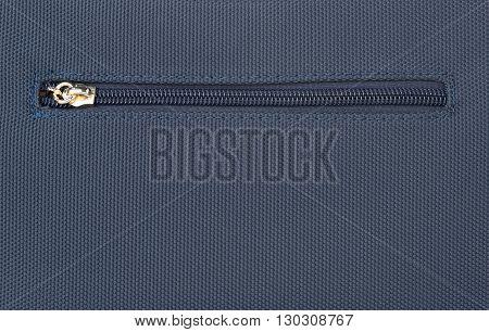 Close up of a zipper on a blue denim background
