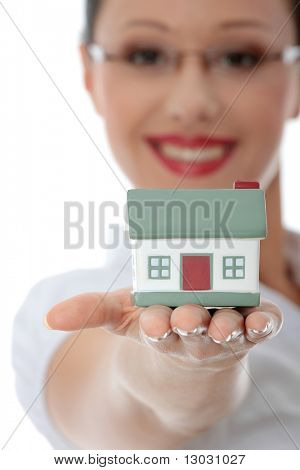 Young beautiful business woman with house model - real estate concept. Isolated on white