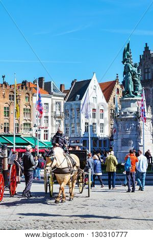 Bruges, Belgium - April 10, 2016: Market place or Grote Markt square with colorful traditional houses, fiaker, people in popular belgian destination
