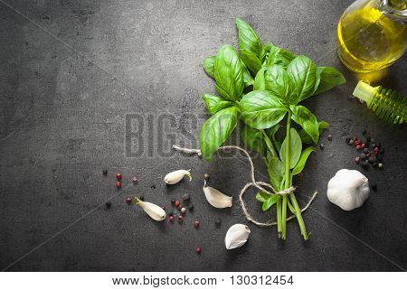 Basil leaves garlic pepper and olive oil at dark slate background. Space for text. Ingredients for cooking.