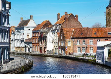 Bruges, Belgium - April 10, 2016: Panorama with canal and colorful traditional houses against cloudy blue sky in popular belgian destination Brugge, Belguim