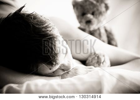 Young Boy Lying On Bed With Teddy Bear