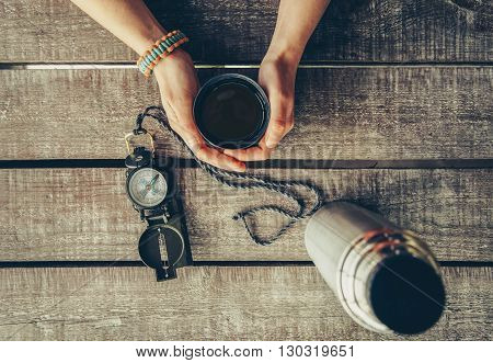 Traveler woman holding a cup of tea on wooden table point of view shot. Thermos and compass on wooden table. Toned image