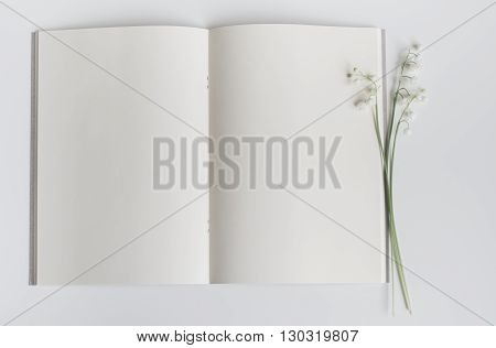 Open empty book with lily of the valley. Blank pages with flower in the middle.