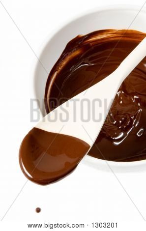 Melted Dark Chocolate Dripping From The Wooden Spoon