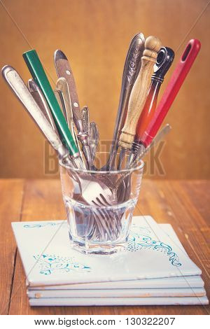 some old spoons and forks in glass on wooden background