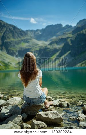 photo of young girl sitting on stone near mountain lake