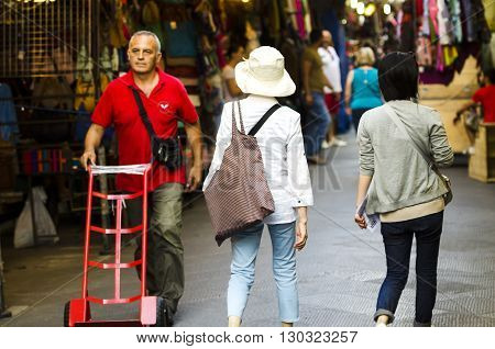 Florence Italy - June 28 2014: Tourists from Eastern origins strolling the local market of Florence on a spring day. The market in the heart of the city specializes in the sale of clothing and leather goods.