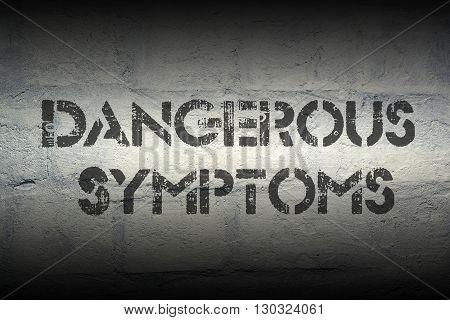 dangerous symptoms stencil print on the grunge white brick wall