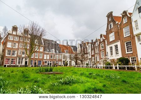 Amsterdam, Netherlands - March 31, 2016: Colorful view of Begijnhof courtyard with historic Holland houses in Amsterdam, Netherlands