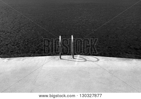 horizontal view of a concrete deck next to the ocean with swimming chrome ladders with no people around